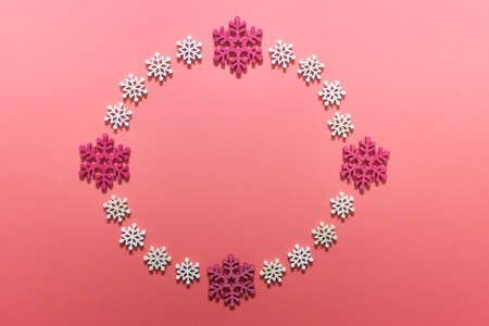 Round Christmas wreath arranged of white and red wooden snowflakes. Greeting card.