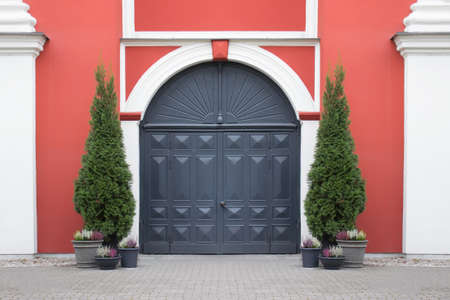 Entrance vintage medieval doors of historical building with symmetrical arrangement of potted decorative plants.