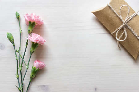 Background with pink flowers, craft paper box present and blank space on wooden background covered with transparent paper. 免版税图像