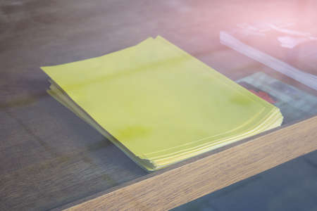 Mockup template of empty blank stack of A4 format yellow paper on table seen from window.