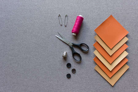 Sewing mockup template with fabric artificial leather squares, scissors, pin, threads and buttons on beige brown background fabric.