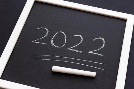 New Year 2022 numbers written in white chalk on black matt paper in white frame. 免版税图像