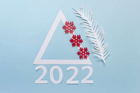 New year 2022 greeting card with red wooden snowflakes and paper palm leaf on blue background.