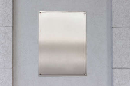 Mockup template empty blank vertical metallic stainless steel sign board on gray wall.