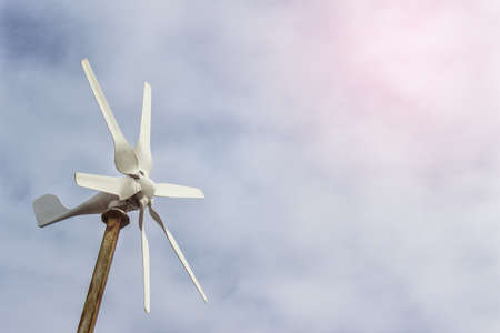 Small windmill wind turbine with blades on the background of sky.