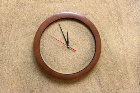 Concept of time - clock filled with sand on real sand background with arrows showing five minutes to twelve.
