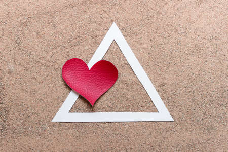 Simple concept of love relationship triangle made of red fabric heart, white paper triangle laying on sand.