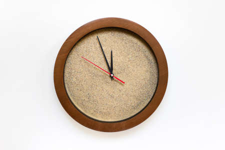 Concept of time - clock filled with real sand with arrows showing five minutes to twelve on white background.