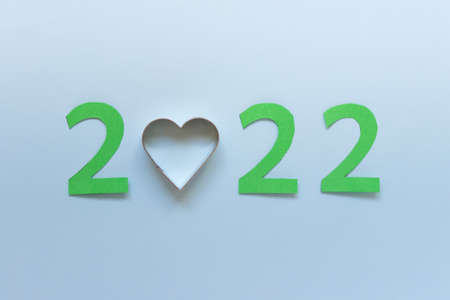 New Year 2022 greeting card with green 2022 numbers and metallic heart shape on blue background.