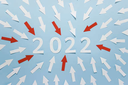 New Year 2022 greeting card with numbers made of white and red paper with poiting arrows on blue background.