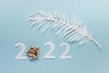 New year 2022 greeting card made of paper numbers, golden bow and white palm leaf on blue paper.