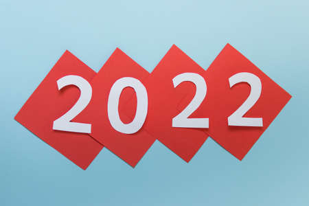 New year 2022 numbers on red paper sheets on blue background.