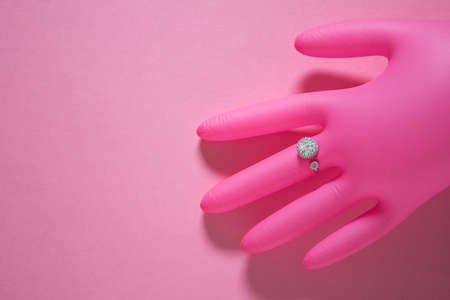 Creative photo with air inflated pink glove and pseudo diamond ring on pink background. 免版税图像