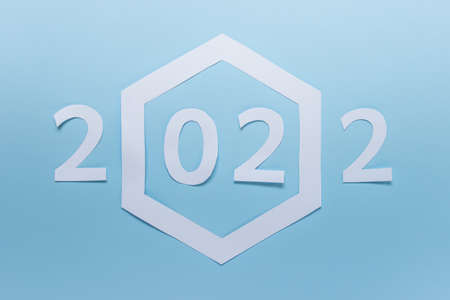 New year 2022 made of paper with large paper hexagon on blue background.