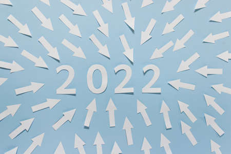 Year 2022 numbers made of white paper with pointing arrows on blue background.