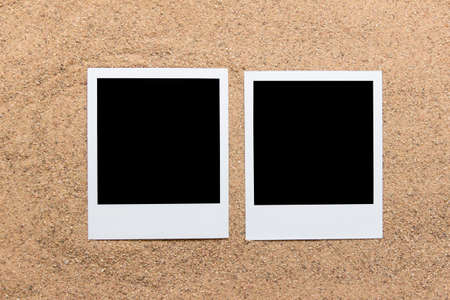 Two paper photos on real sand with little grains visible.