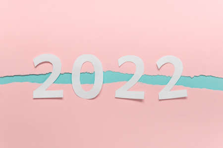 Year 2022 numbers made of paper on double colored paper with ripped edges.
