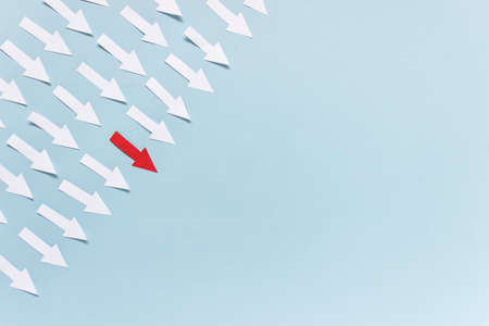 White paper arrows with red one pointing to center on blue background. Photo with copy blank space.
