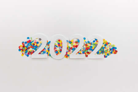 New Year 2022 greeting card with white paper numbers on real colorful confetti on white background. 免版税图像