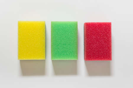 Three dish washing sponges colored with yellow green red on white background.