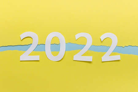 Year 2022 numbers made of paper on yellow paper with ripped edges.