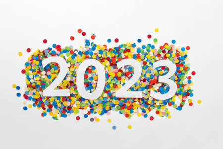 New year 2023 number made of white paper arranged on colorful confetti on white paper.