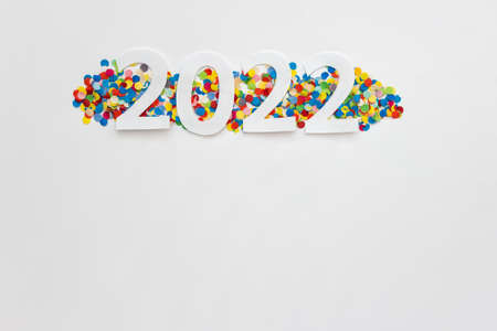 New Year 2022 greeting card with white paper numbers on real colorful confetti on white background. Photo with copy blank space.