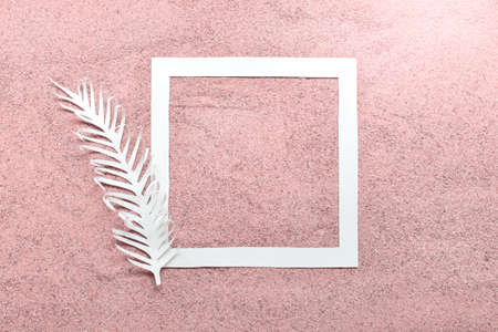 Mockup template with white paper square and white feather on real sand colored with pink color. 免版税图像