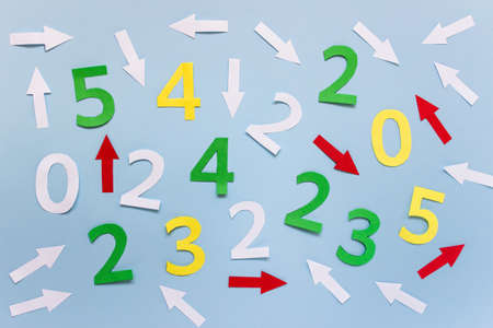 Random arrangement of many colorful numbers and arrows on blue paper.
