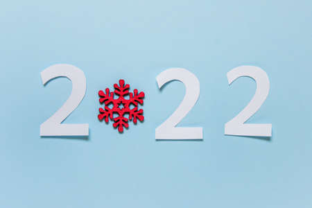 New year 2022 celebration greeting card with paper numbers and wooden large snowflake on blue background.