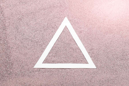Simple concept white paper triangle on pink real sand background.