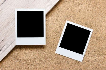 Two paper photos cards with blank copy space on wood and real sand background.
