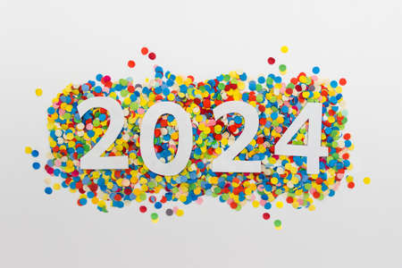 New year 2024 number made of white paper arranged on colorful confetti on white paper. 免版税图像