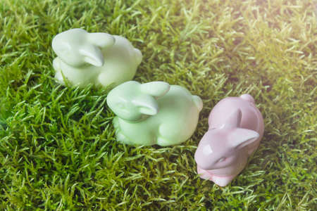 Easter composition with three porcelain figurines on green grass. 免版税图像