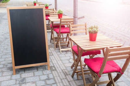 Mockup template with summer outside cafe seating setting place and blank black menu charcoal board.