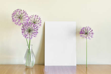 Mockup template with A4 paper and summer flowers in glass vase on wooden shelf.