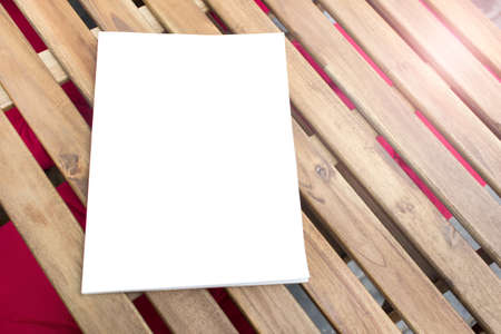 Mockup template of paper book with blank cover laying diagonally on wooden table.