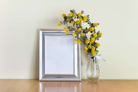 Blank silver frame with yellow flowers in glass vase standing on wooden surface.