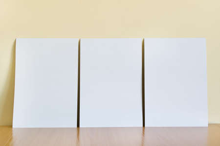 Three white A4 blank paper sheets standing on wooden shelf on the background of yellow wall.