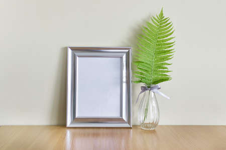 Blank metallic silver frame with blank space and wild forest fern leaf in glass vase on wooden surface.