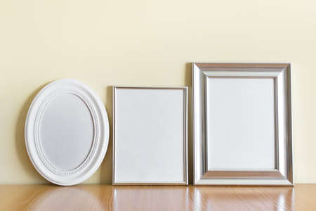 Mockup template with three frames - white oval frame, silver A4 frame, and wide silver frame on wooden shelf.