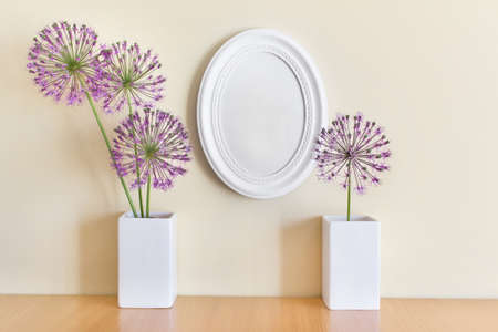 Composition with blank white oval frame and porcelein two white vases and summuer purple flowers.