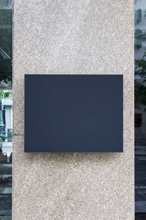 Vertical shop exterior with black blank board hanging on concrete wall.