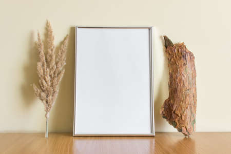 Mockup template with A4 silver frame and wooden log, dry yellow plants on wooden surface.