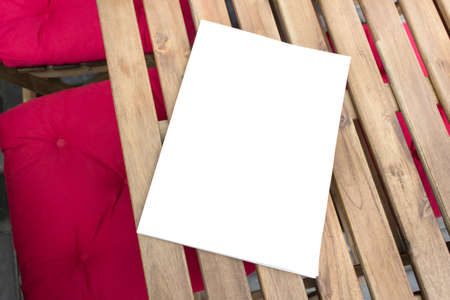Mockup template of paper book with blank cover laying on wooden table on terrace of outside cafe. 免版税图像