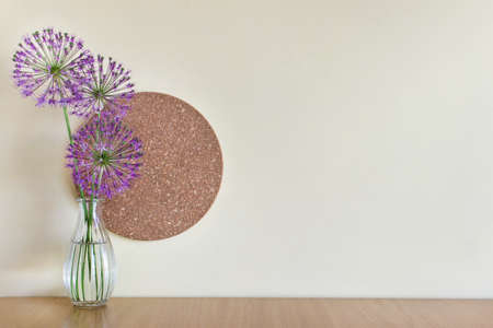Blank wall mockup with simple composition with glass vase, pink summer flowers and round cork material. Image with blank wall.
