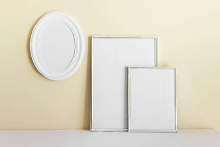 Mockup template with tree frames - white oval frame, A4 and A3 on background of yellow wall.