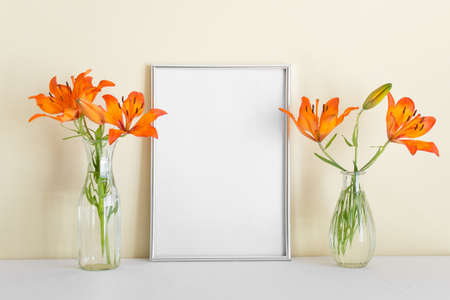 A4 blank silver frame with blank empty space surface, orange lily standing on white surface. 免版税图像
