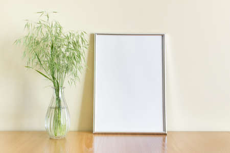 Mockup template with vertical A4 blank silver metallic frame with green wild forest plants in glass vase on wooden shelf.