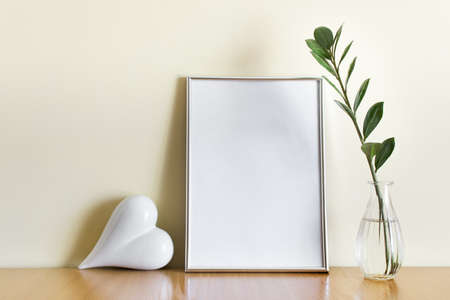 Mockup template with A4 silver frame and white romantic heart, green plant branch in glass vase. 免版税图像